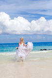 The bride in wedding a dress runs on ocean coast Stock Images
