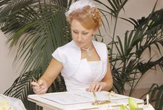 The bride in a wedding dress signs the marriage documents royalty free stock photography