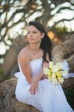 Bride in wedding dress sits on the tree roots in the middle of tropical trees with a bouquet in her hand royalty free stock photography