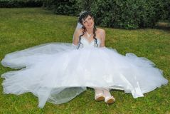 The bride in a wedding dress is sitting on the grass. A girl in a white dress looks away royalty free stock photo