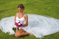 Bride in Wedding Dress Sitting on Grass Stock Photo