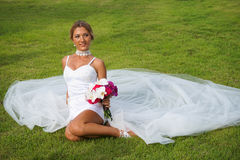 Bride in Wedding Dress Sitting on Grass Stock Photos