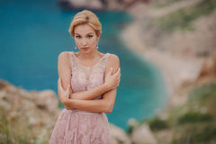 Bride in wedding dress standing on a rock Royalty Free Stock Photos