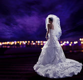 Bride in Wedding Dress with Veil, Fashion Bridal Beauty Portrait. Long Draped Cloth with Folds, Rear View over Night City Lights Sky Stock Photo