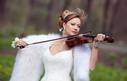 Bride in a wedding dress with a violin Royalty Free Stock Photos