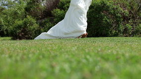 Bride in wedding dress walking on grass Stock Photography