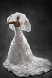 Bride in wedding luxury dress, back view. Black background. Bride in wedding luxury dress, back side view, raised hands up with veil. Black background royalty free stock image