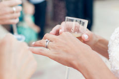 Bride with wedding ring holds a glass of champagne Stock Photo