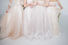 Bride in wedding salon. Four beautiful girl are in each other`s arms. Back, close-up lace skirts. Bride in wedding salon. Four beautiful girl are in each other`s Royalty Free Stock Image