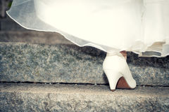 Bride in wedding shoes and dress on stairs Royalty Free Stock Photography