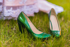 Bride wedding shoes. Wedding emerald bridesmaid shoes on the green grass on the background of the dress Stock Image