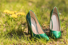 Bride wedding shoes. Wedding emerald bridesmaid shoes on the green grass on the background of the dress Stock Photography