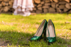 Bride wedding shoes. Wedding emerald bridesmaid shoes on the green grass on the background of the dress Stock Photo