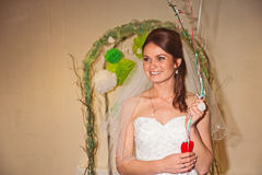 Bride welcomes guests. Smiling bride in a Mr and Mrs arch welcoming guests to the reception Stock Photography
