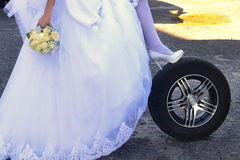 The bride with a wheel. The bride wedding car repair, Wedding background Stock Photography