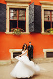 Bride whirls before a groom standing behind an orange house Royalty Free Stock Images