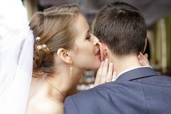 Bride is whispering I love you into his groom ear.  stock photo