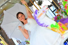 Bride on a white carousel horse Stock Image