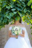 A bride in a white dress with a bouquet in her hands is standing in the garden. I put my head in the tree stock photo