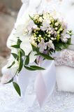 Bride in white dress and bridal bouquet in hand Stock Photo