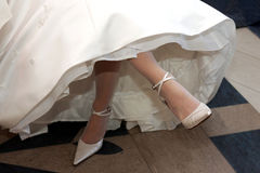 Bride in white dress crossing legs Royalty Free Stock Photography