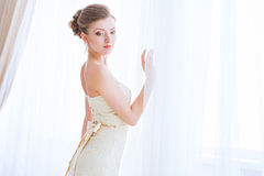 The bride in a white dress about curtains. Royalty Free Stock Images