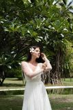 A bride in a white dress with an exotic flower in her hair is standing under a flowering tropical tree. Wedding on a tropical island stock images