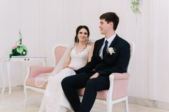 The bride in a white dress and groom in a blue suit are sitting in the room and holding a wedding bouquet. Close-up portrait. Happ. Y newlywed Royalty Free Stock Photos