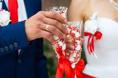 Bride in white dress and groom in dark blue suit clink glasses with beautiful handmade glasses at the wedding table stock image