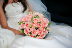 Bride in white dress holding bouquet of roses Stock Photo