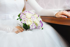 Bride in white dress holding bouquet of roses Stock Photos