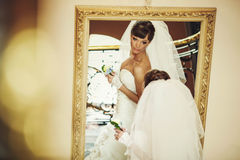 Bride in white dress holding flower and looking at the miror Stock Image