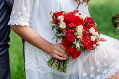Bride in white dress holding in hands delicate, expensive, trendy bridal wedding bouquet of flowers in marsala and red colors. Clo. Se up, top view Stock Photography