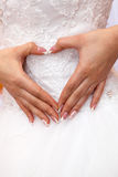 The bride in  white dress holding hands in a heart shape. Royalty Free Stock Photography