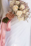 Bride in white dress holding a wedding bouquet of roses Stock Image