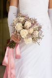Bride in white dress holding a wedding bouquet of roses Stock Photos
