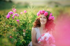A bride in a white dress holds a bouquet of roses and callas on the background of green grass. stock images