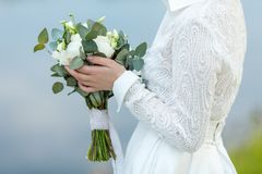 Bride in white dress holds wedding bouquet in front of her.  Royalty Free Stock Image