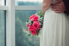 Bride in a white dress hugs her husband, she was standing at the window Royalty Free Stock Photos