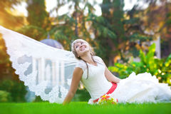 Bride in a white dress is lying on the green grass Royalty Free Stock Photography