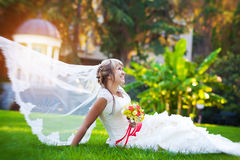 Bride in a white dress is lying on the green grass. Beautiful bride in a white dress is lying on the green grass Stock Images