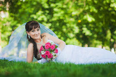 Bride in white dress lying on green grass Royalty Free Stock Images