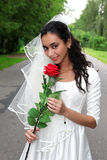 Bride in white dress with red flower Royalty Free Stock Images