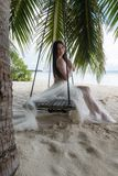 A bride in a white dress is riding on a swing under a big palm tree. Wedding on a tropical island stock image