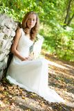 Bride in white dress sits near a stone wall Royalty Free Stock Images
