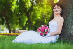 Bride in white dress sitting under a tree Stock Image