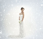 A bride in a white dress on a snowy background Royalty Free Stock Image