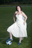 Bride in white dress on a soccer field. Royalty Free Stock Image