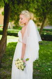 Bride in white dress standing near tree park Stock Photo