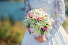 Bride in a white dress in summer green park with a bouquet in ha Royalty Free Stock Photo